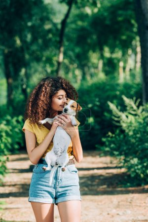 young, curly woman in summer outfit kissing jack russell terrier dog in park