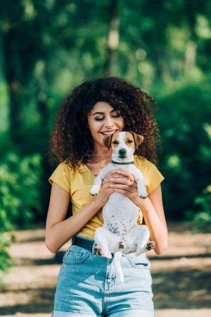 Photo pour Femme joyeuse en tenue d'été tenant Jack Russell terrier chien dans le parc - image libre de droit