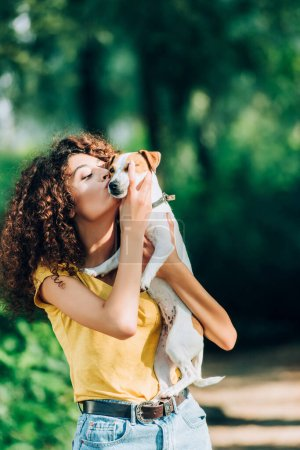 young woman in summer outfit kissing jack russell terrier dog in park