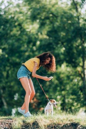Photo pour Jeune femme en tenue d'été riant tout en prenant une photo de Jack Russell terrier chien dans le parc - image libre de droit