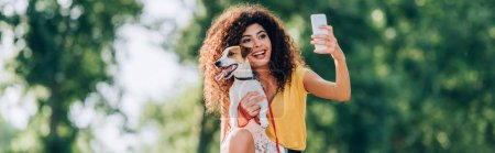 Photo for Horizontal concept of excited woman taking selfie on mobile phone with jack russell terrier dog - Royalty Free Image