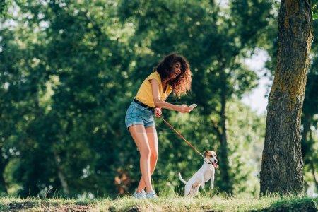 Photo pour Femme rieuse en tenue d'été prendre des photos de Jack Russell terrier chien tout en se promenant dans le parc - image libre de droit