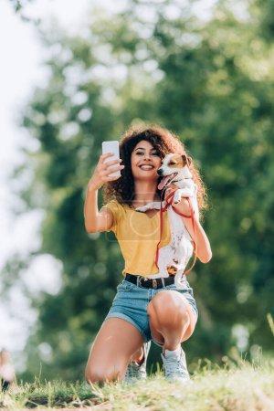 Photo pour Femme excitée en tenue d'été tenant Jack Russell Terrier chien tout en prenant selfie sur smartphone dans le parc - image libre de droit