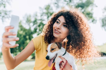 Photo for Young, curly woman cuddling jack russell terrier dog while taking selfie on cellphone in park - Royalty Free Image