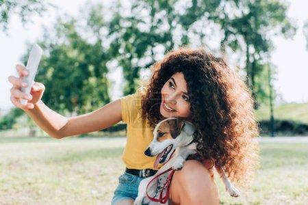 Photo pour Femme joyeuse prenant selfie sur smartphone avec Jack Russell terrier chien dans le parc - image libre de droit
