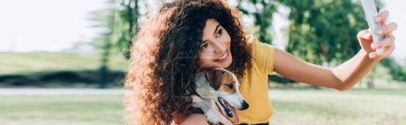 Photo for Panoramic crop of curly woman taking selfie on smartphone with jack russell terrier dog - Royalty Free Image
