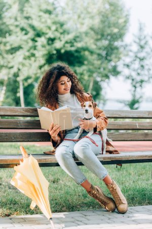 stylish woman in autumn outfit holding book and hugging jack russell terrier dog on bench in park