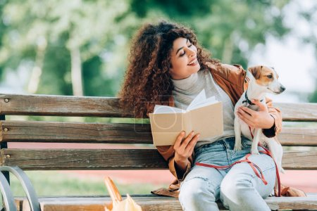 laughing woman cuddling jack russell terrier dog while sitting on bench with book