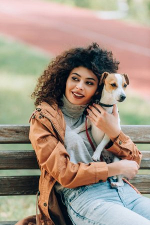 stylish woman in autumn outfit looking away while cuddling jack russell terrier dog on bench in park
