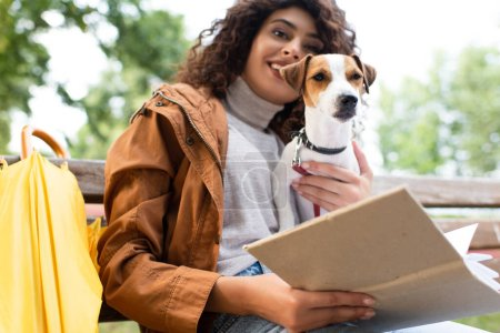 selective focus of joyful woman looking at camera while sitting in park with book and jack russell terrier dog