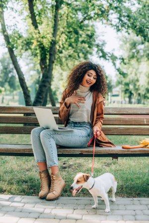 Photo pour Excité freelancer toucher la poitrine tout en étant assis sur le banc avec ordinateur portable et Jack Russell terrier chien en laisse - image libre de droit