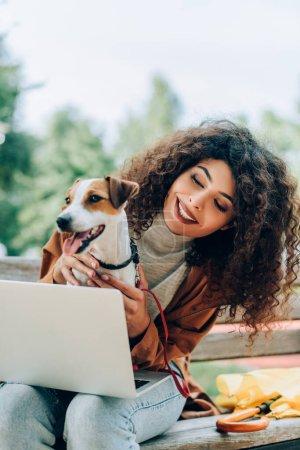 joyful freelancer cuddling jack russell terrier dog while sitting on bench with laptop