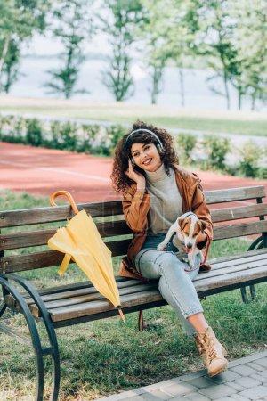 Photo pour Femme élégante dans les écouteurs sans fil tenant jack russell terrier chien assis sur le banc près du parapluie jaune - image libre de droit