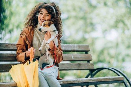 brunette, femme bouclée dans des écouteurs sans fil regardant loin tout en étant assis dans le parc avec Jack Russell Terrier chien