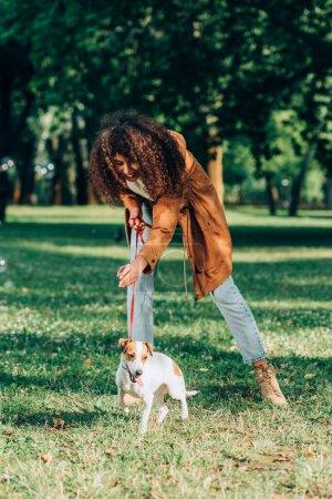Photo pour Focus sélectif de la femme bouclée en imperméable jouant avec Jack Russell Terrier dans le parc - image libre de droit