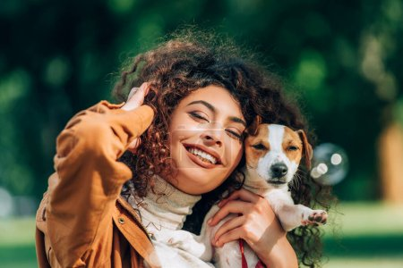 Enfoque selectivo de la joven mujer rizada con la mano cerca de la cabeza sosteniendo jack russell terrier al aire libre