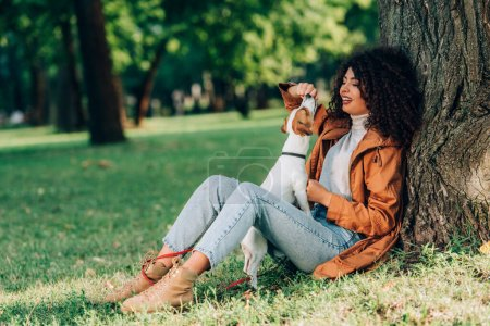 Selektiver Fokus einer Frau im Regenmantel, die mit Jack Russell Terrier in der Nähe eines Baumes im Park spielt