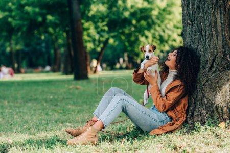 Selektiver Fokus der lockigen Frau in Jeans und Regenmantel, die Jack Russell Terrier in der Nähe eines Baumes im Park hält