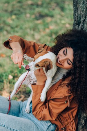 Selective focus of woman in autumn outfit playing with jack russell terrier in park