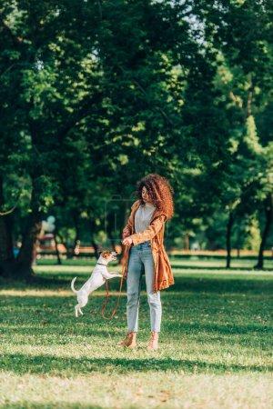 Photo pour Focus sélectif de la jeune femme jouant avec jack sautant russell terrier en laisse dans le parc - image libre de droit