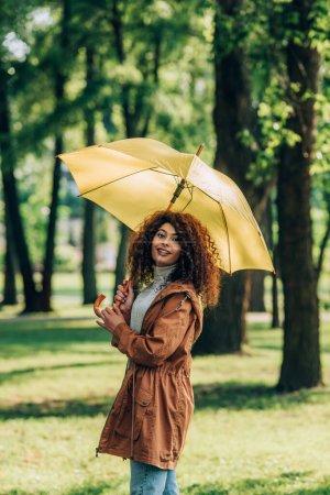 Femme bouclée en imperméable tenant parapluie et regardant la caméra dans le parc