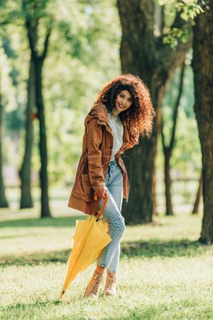 Selective focus of curly woman holding yellow umbrella on lawn in park