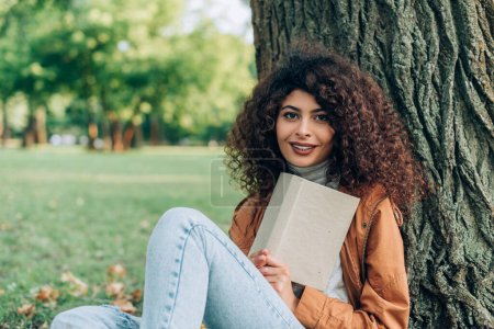 Selective focus of curly woman in raincoat holding book near tree in park