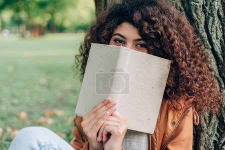 Photo for Selective focus of curly woman holding book near face in park - Royalty Free Image