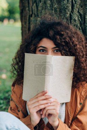 Enfoque selectivo de la mujer mirando la cámara mientras sostiene el libro en el parque