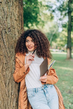 Photo for Curly woman in raincoat holding pen and notebook near tree in park - Royalty Free Image