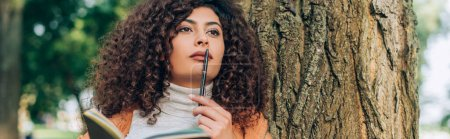 Photo pour Récolte horizontale de femme rêveuse avec stylo et cahier regardant loin près de l'arbre - image libre de droit