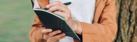 Photo pour Récolte panoramique de femme écrivant sur un carnet près d'un arbre - image libre de droit