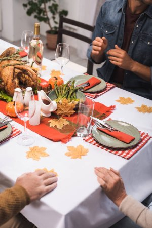 cropped view of parents and son sitting at table served with thanksgiving dinner