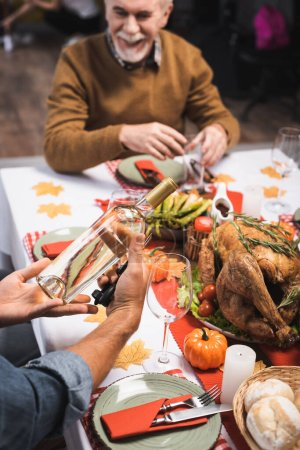 selective focus of man holding bottle of white wine while sitting at table served with thanksgiving dinner