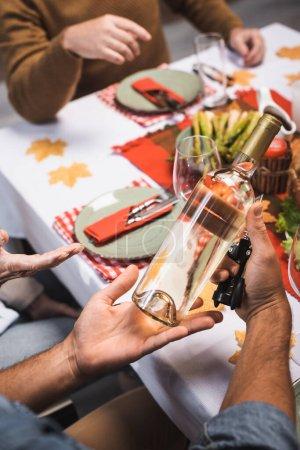 Photo pour Vue recadrée de l'homme tenant une bouteille de vin blanc pendant le dîner d'Action de grâces en famille - image libre de droit