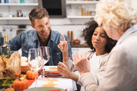 Photo pour Foyer sélectif de fille afro-américaine montrant geste idée tout en célébrant thanksgiving avec la famille - image libre de droit