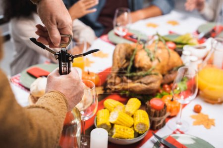 partial view of senior man opening bottle of white wine with corkscrew during thanksgiving dinner with multiethnic family