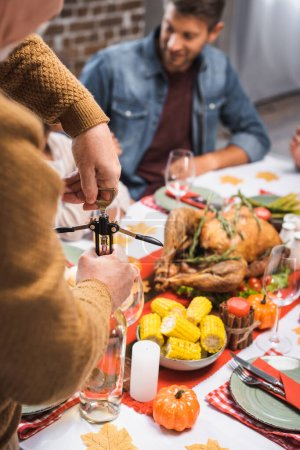 selective focus of senior man opening bottle of white wine during thanksgiving celebration with family
