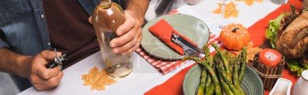Photo pour Vue recadrée de l'homme tenant une bouteille de vin blanc et tire-bouchon à table servi avec dîner d'action de grâces, image horizontale - image libre de droit