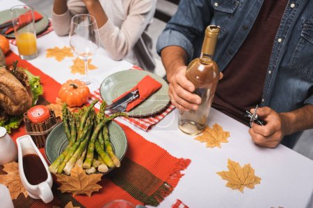 cropped view of man holding bottle of wine while sitting near african american girl during thanksgiving dinner