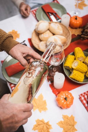 Photo pour Vue recadrée de l'homme âgé versant du vin blanc pendant la célébration du jour de l'Action de grâce - image libre de droit