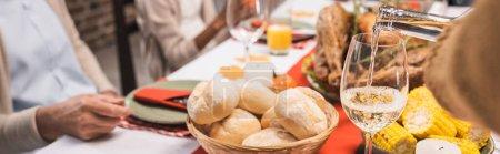 Photo pour Foyer sélectif de délicieux petits pains, maïs et verre de vin blanc sur la table, servi le jour de l'Action de grâces près de la famille multiculturelle, culture panoramique - image libre de droit
