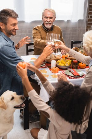 selective focus of african american girl holding decorative pumpkin near golden retriever and family celebrating thanksgiving day