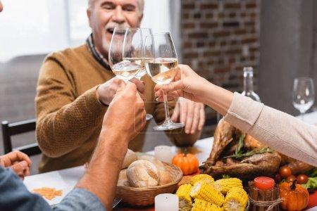 Photo pour Famille cliquetis verres de vin blanc pendant le dîner de Thanksgiving - image libre de droit
