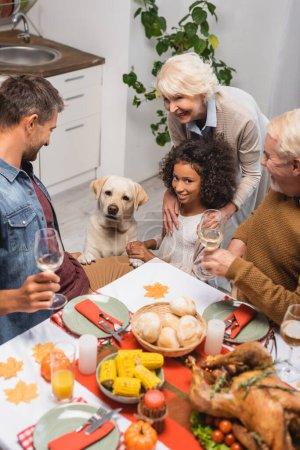 multicultural family and golden retriever near table served with festive thanksgiving dinner