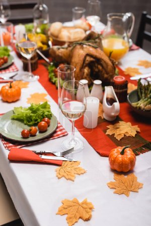 selective focus of table served with traditional thanksgiving dinner, decorated with foliage, candles and pumpkins