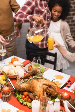Photo for Cropped view of multicultural family pouring beverages at table served with delicious thanksgiving dinner - Royalty Free Image
