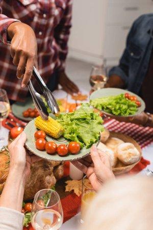 Photo pour Vue partielle de la femme âgée tenant une assiette avec du maïs, de la laitue et des tomates cerises pendant le dîner d'action de grâce avec une famille multiethnique - image libre de droit