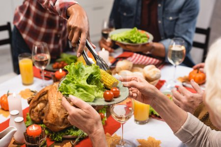 cropped view of senior woman holding plate with vegetables during thanksgiving dinner with multicultural family