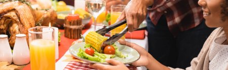 Photo for Cropped view of mother putting corn on plate for african american daughter during thanksgiving dinner, panoramic shot - Royalty Free Image